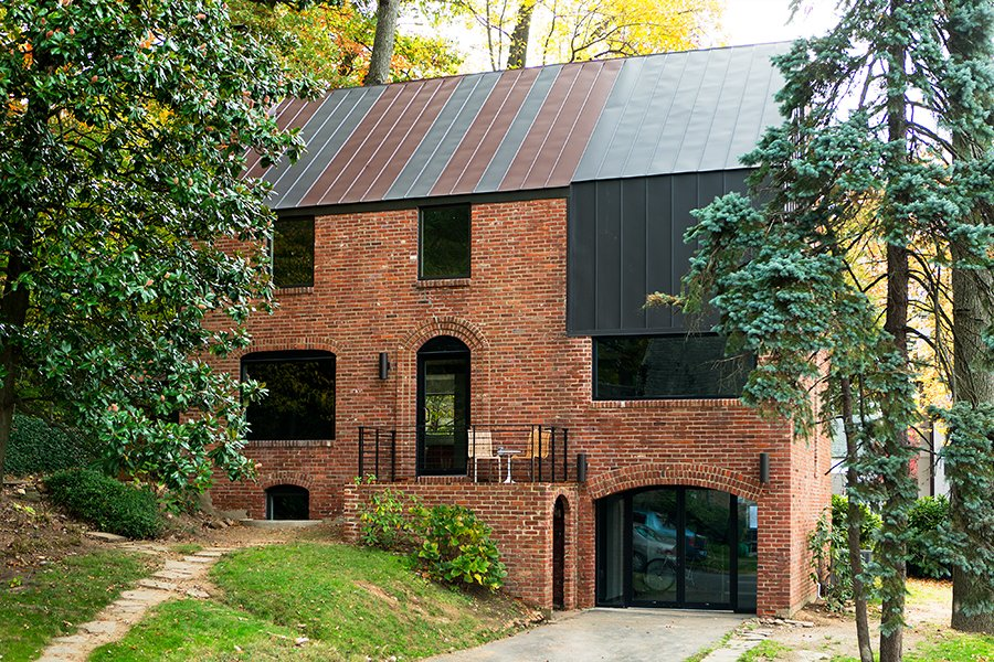 In Arlington, Virginia, a drafty house was made more than twice as efficient with the addition of metal both inside and out. Roof panels topping the brick envelope echo its original geometry. Tagged: Exterior, Brick Siding Material, and Metal Roof Material.  Photo 1 of 5 in Steel Preserve