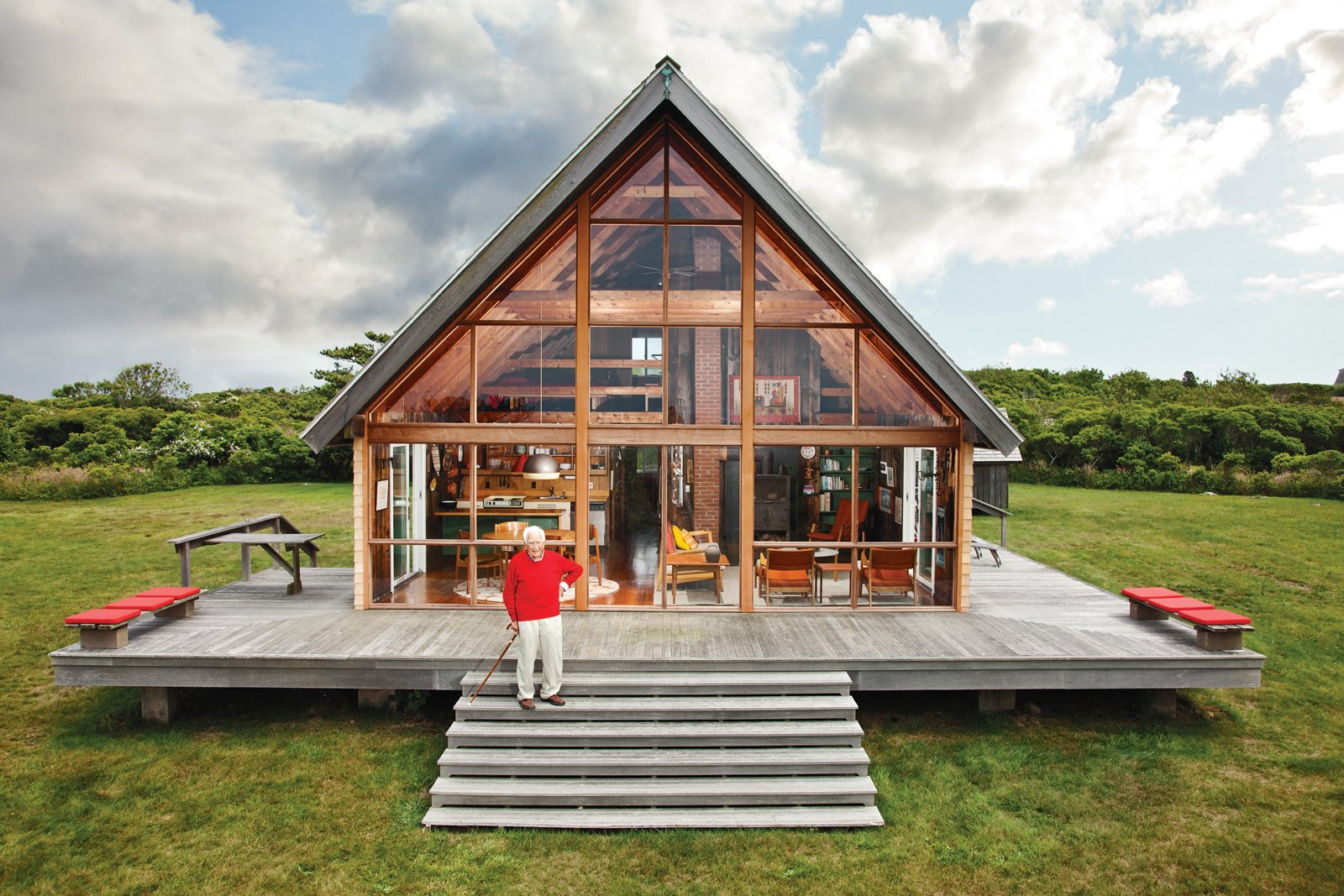 Outdoor, Front Yard, and Wood Patio, Porch, Deck In 2009, Dwell editor-in-chief Amanda Dameron joined Jens Risom on his return to his 1967 prefab off the coast of Rhode Island, where he's been readying it for his family's next generation. The A-framed structure, shown here, is bordered by a low stone wall, an aesthetic element that appears throughout the land.  Photo 2 of 9 in Happy 100th Birthday, Jens Risom