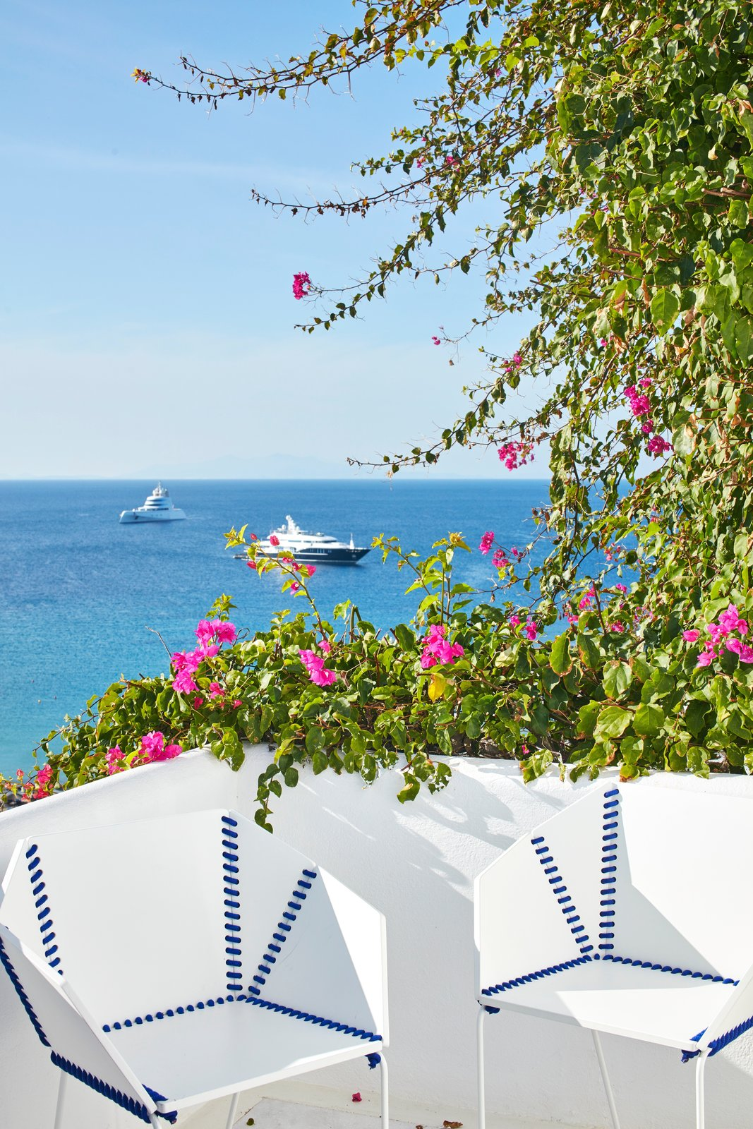 Outdoor, Trees, Back Yard, and Flowers The color of royal blue appears throughout the hotel and pops against the bright white foundations—both indoors and out.  Photo 3 of 12 in This Revived Greek Resort Will Soon Be at the Top of Your List