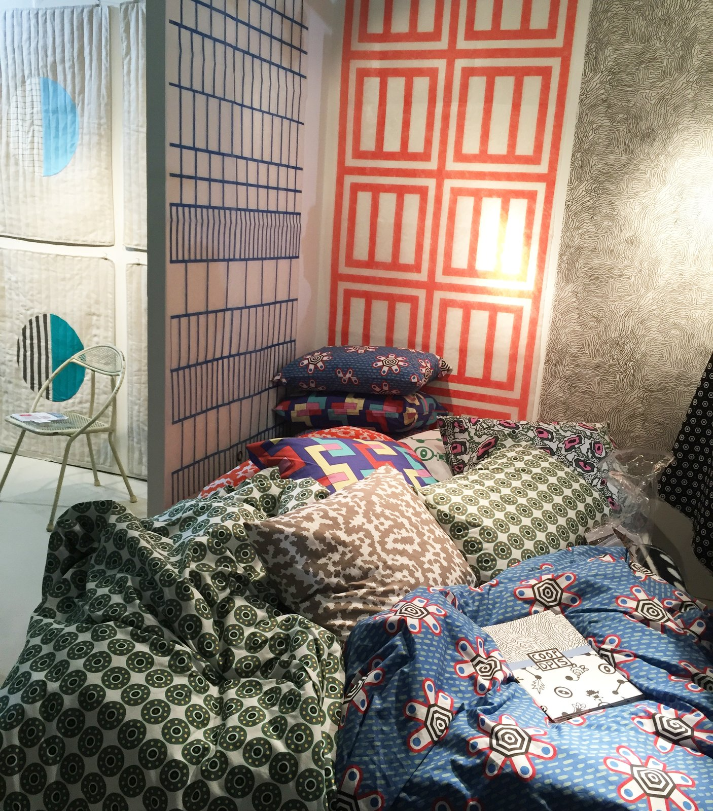 From ZigZag Zurich's colorful booth, the CoopDPS collection of wallpaper, fabric, and bedding was designed by Nathalie Du Pasquier and George Sowden, two of the founding members of the Memphis Design group. #DwellNow #sightunseenoffsite #zigzagzurich #coopdps #memphisdesign #pattern #bedding #wallpaper #color #nathaliedupasquier #georgesowden  Photo 36 of 42 in Wallpaper That Fixes Walls
