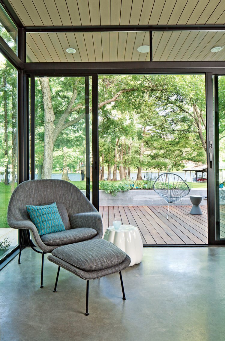 Saarinen Womb Chair upholstered in Knoll fabric is accented by a Maharam pillow and a ceramic Oppiacei pouffe from Skitsch. Acapulco chairs, handmade by Greenpoint Works in Brooklyn, and a Prince Aha stool by Philippe Starck for Kartell grace the deck outside.  Photo 4 of 7 in The Lakeside Getaway That Entertains All Ages