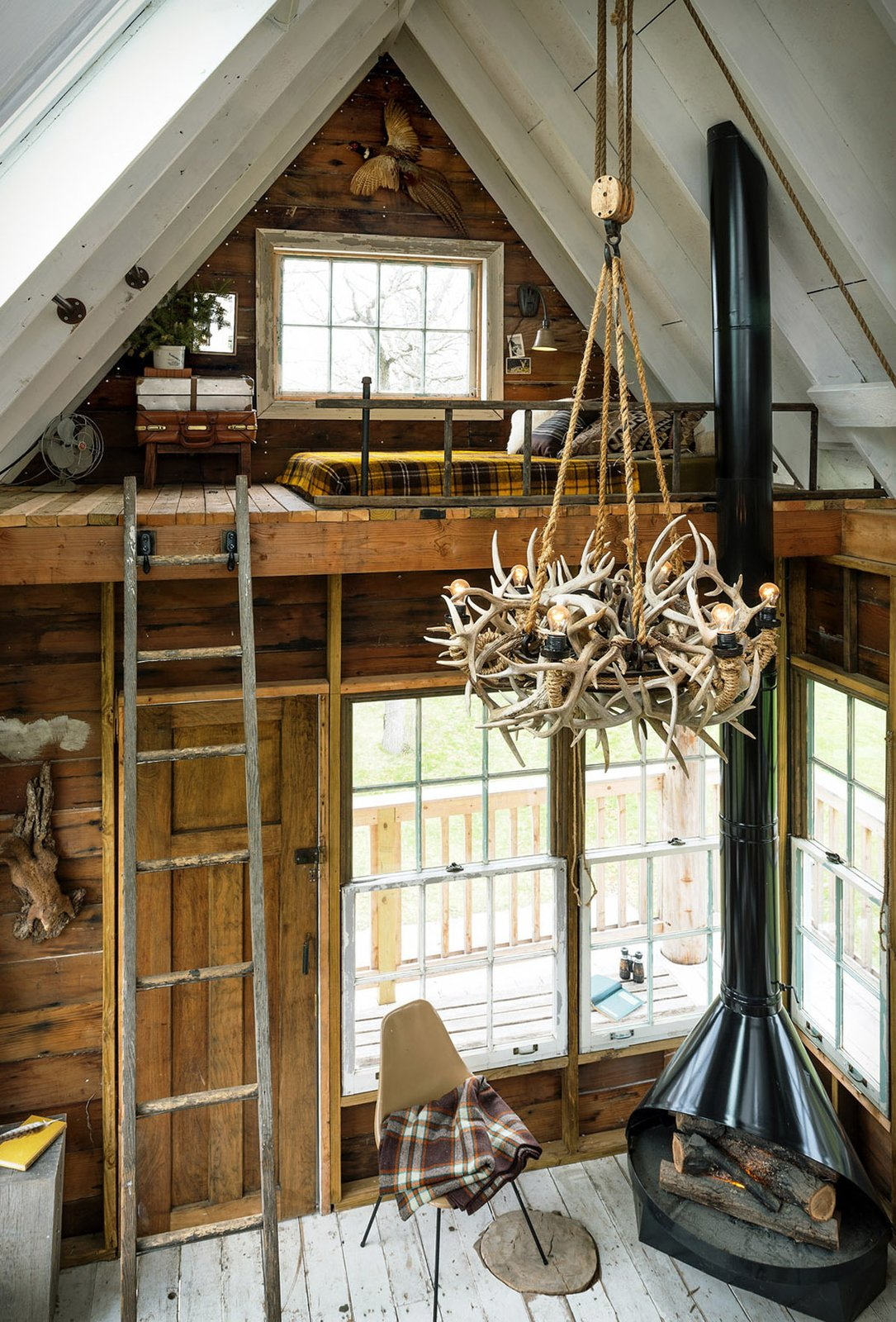 The interior of a treehouse at the camp features a wood-burning stove and antler chandelier.  Photo 7 of 9 in This is How You Combine Modern Architecture, Flea Market Finds, and Art All Together