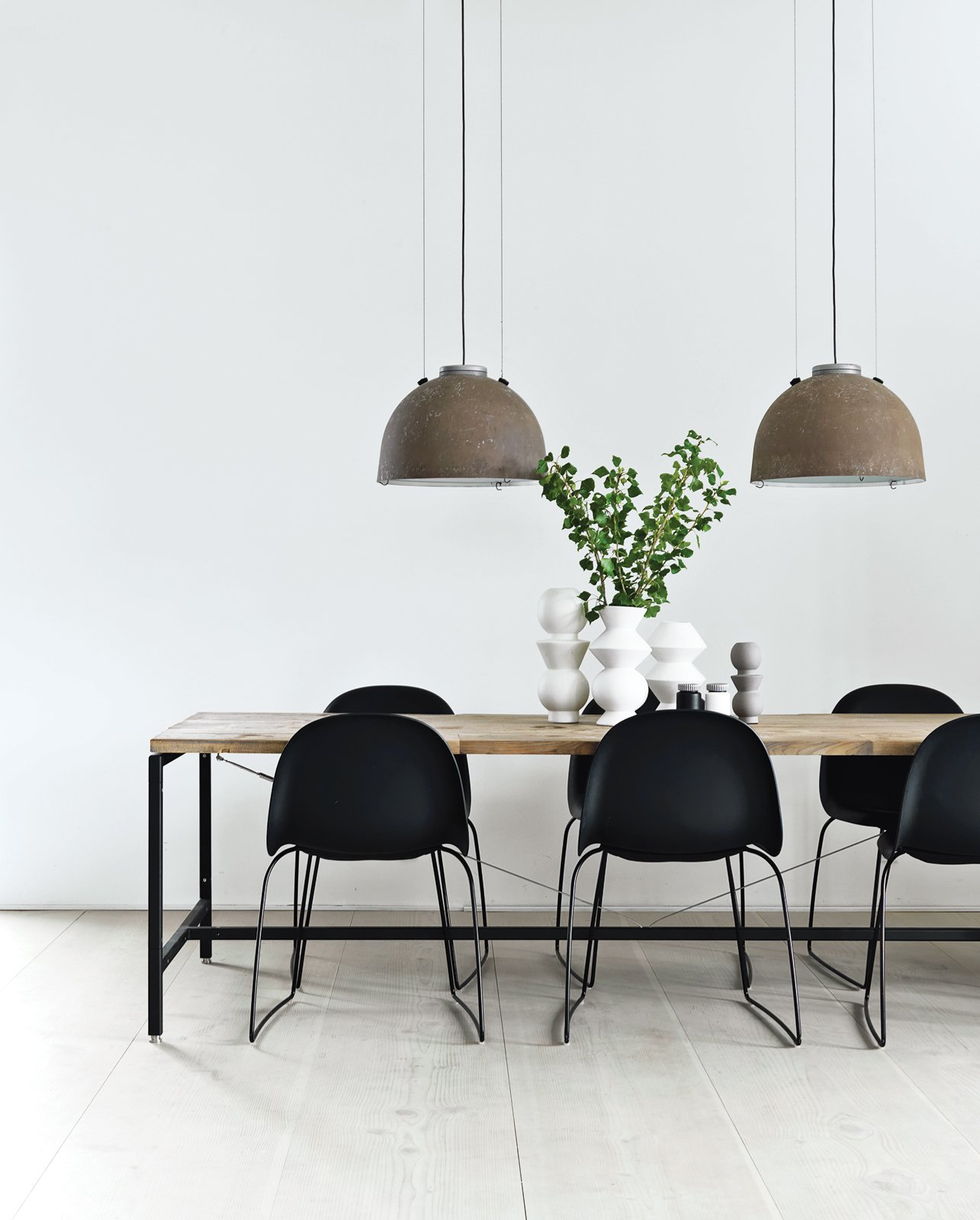 Morten Bo Jensen, of Danish industrial design company Vipp, and his partner, graphic designer Kristina May Olsen, have mixed repurposed vintage items with their own creations inside their Copenhagen apartment. In the kitchen, the dining table—Jensen's first piece for Vipp—is made of powder-coated aluminum frame with a recycled, untreated teak top. The lamps overheard are salvaged and rewired Copenhagen streetlights.  Photo 2 of 8 in Two Designers Sharpen Up This Former Pencil Factory
