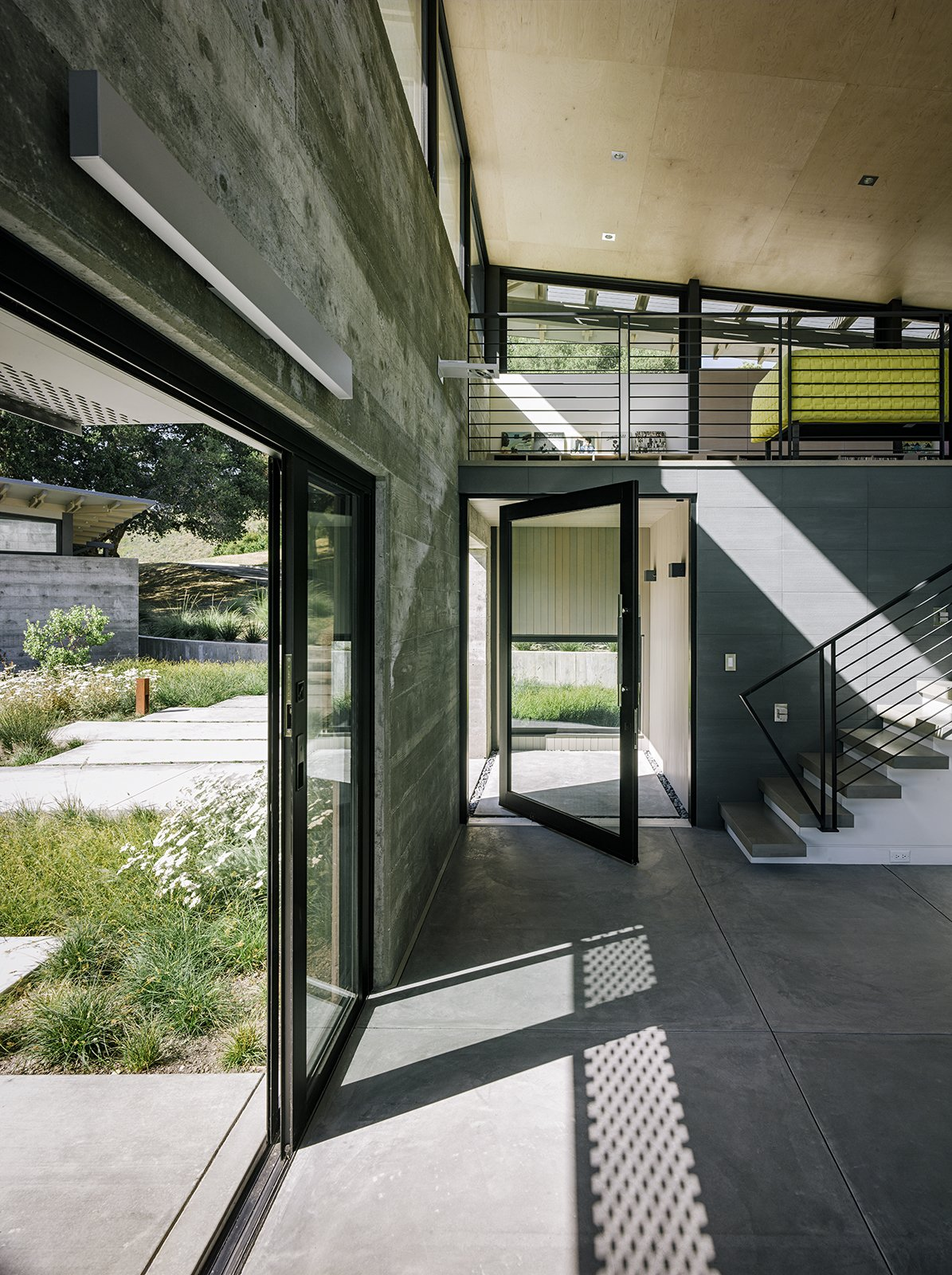 The entrance to the main pavilion is defined by a pivoting glass door from Fleetwood (above left). The stairs lead to the media loft, where Inga Sempé's Ruché sofa for Ligne Roset breaks up the gray. Among the couple's few directives were tall ceilings, which Feldman covered in low-cost plywood sheets.  Photo 6 of 11 in Retirement Never Looked Better and More Sustainable