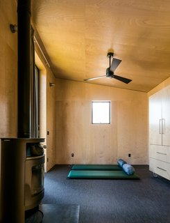 The family keeps the plywood-lined interiors sparse, using campaign furniture and sleeping bags when they stay here; the floor coverings are by Chilewich, and the wood-burning stove is by Rais.