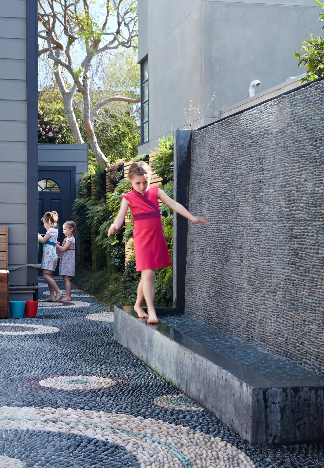 Outdoor, Back Yard, Front Yard, and Side Yard The water wall was one of the family's main requests. Not only does it provide the girls— Serafina, Carolina, and Madeleine—a place to play, it also blocks street noise.  Photo 5 of 6 in A Heavenly Backyard is Precise with Pebbles