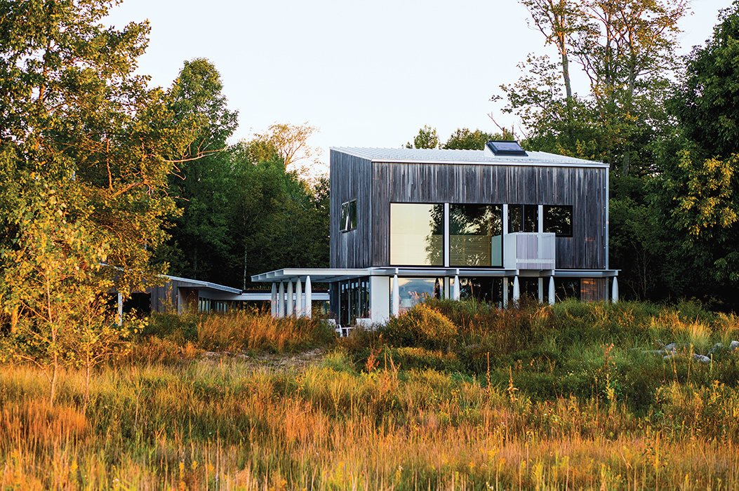 Brogan's home overlooking Lake Michigan is clad in tongue-and-groove new-growth cypress. Vertical basswood slats follow the stairs to the second floor and into the master bedroom, extending outside to serve as the railing for a small balcony.  Photo 5 of 7 in A Lakeside Home Brings a Scandinavian Sensibility to the Midwest