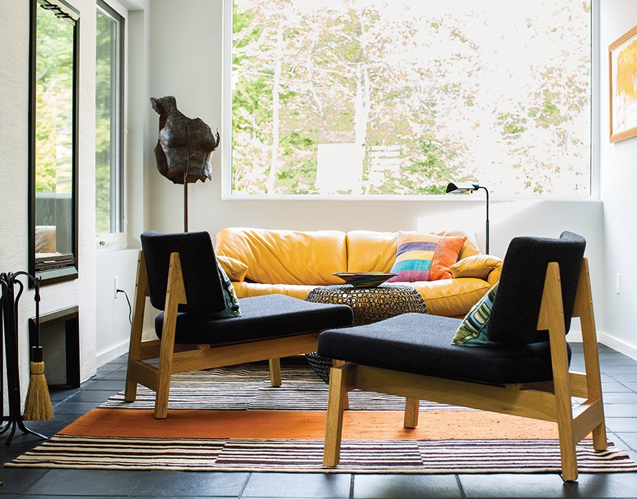 """One end of the gathering hall is furnished with a pair of lounge chairs and an iron side table, all from CB2 and since discontinued. Brogan designed the rug and had it made at the Mehmet Çetinkaya Gallery in Istanbul. Brogan says she chose the Maralunga sofa by Vico Magistretti for Cassina """"for the color and the scale in a small area near the tiny fireplace.""""  Photo 6 of 7 in A Lakeside Home Brings a Scandinavian Sensibility to the Midwest"""