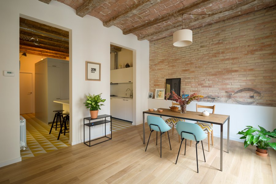 A confused layout meant that the original apartment had a series of dark, confined rooms. The designers eliminated a third bedroom and enlarged the living room. The previous kitchen was separated from the living area by a tight hallway. Nook's reconfiguration attached the kitchen directly to the living room, at the client's request.  Photo 3 of 6 in In Barcelona, Vaulted Ceilings Are Always a Win