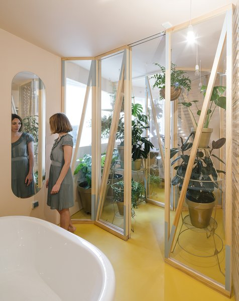 A small greenhouse is place between the two most humid areas in the apartment: the bath, and a smaller, more private shower room.