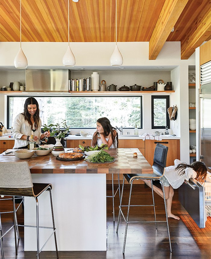 Kitchen, Wood, Dark Hardwood, Wood, and Pendant In the kitchen, designer Maca Huneeus prepares lunch with her daughters Ema, 12, and Ofelia, 7. The pendants are Jonathan Adler; the island is a custom design, inspired by a 1960s Dansk tray that belonged to Huneeus's mother. The barstools are from Blu Dot.  Best Kitchen Dark Hardwood Wood Photos from The Ski Retreat for All Seasons