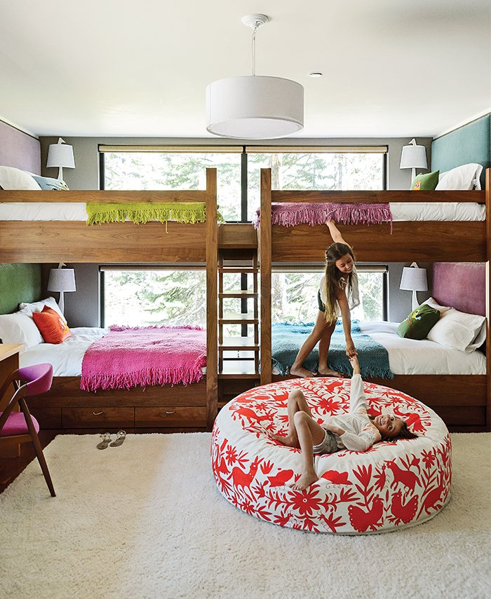 Kids Room, Bunks, Bedroom Room Type, and Rug Floor In the kids' bunk room, Maca designed walnut beds with built-in storage and fabric headboards, and covered each one in hand-knit blankets by Marcela Rodriguez-Chile. The giraffe sconces are from Jonathan Adler. The girls play on a hand-embroidered Olli lounger from Heath Ceramics.  Photos from The Ski Retreat for All Seasons