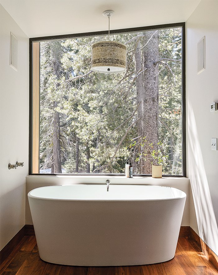 Bath, Freestanding, and Medium Hardwood In the master bathroom, a matte Ove tub from Wetstyle is one of Maca's favorite getaways. The angle of the custom window, designed with a minimal frame to maximize the view, mimics the roofline.  Dwell's Favorite Bath Medium Hardwood Photos from The Ski Retreat for All Seasons