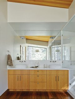 """Talo Mini chrome sconces from Artemide installed atop the mirror in the master bathroom effectively disappear, becoming what Maca calls """"subtle 3-D sculptures."""" The Neo Blanco vanity, from Porcelanosa, is clad in the same Douglas fir as the ceiling. The IQ faucets are from Jado."""