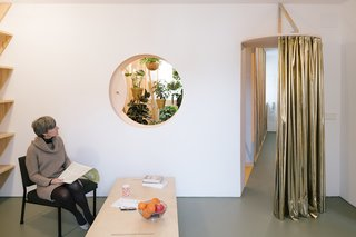 A cutout oculus in the living room offers a peek into the plant-filled bath, while a curtain can be drawn to control airflow.