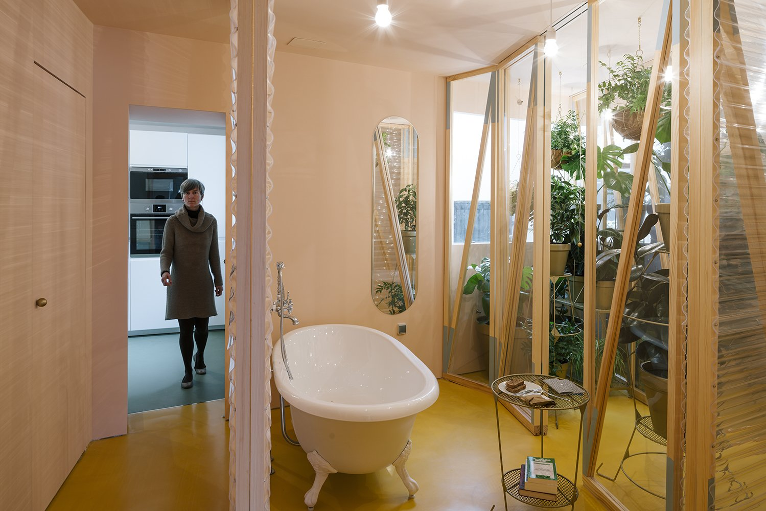 The bathroom is located at the heart of the apartment, with sliding plastic doors of varying transparency that can be moved into a number configurations.  Photo 6 of 7 in A Quirky Renovation Brings an Indoor Garden to the Center of Madrid