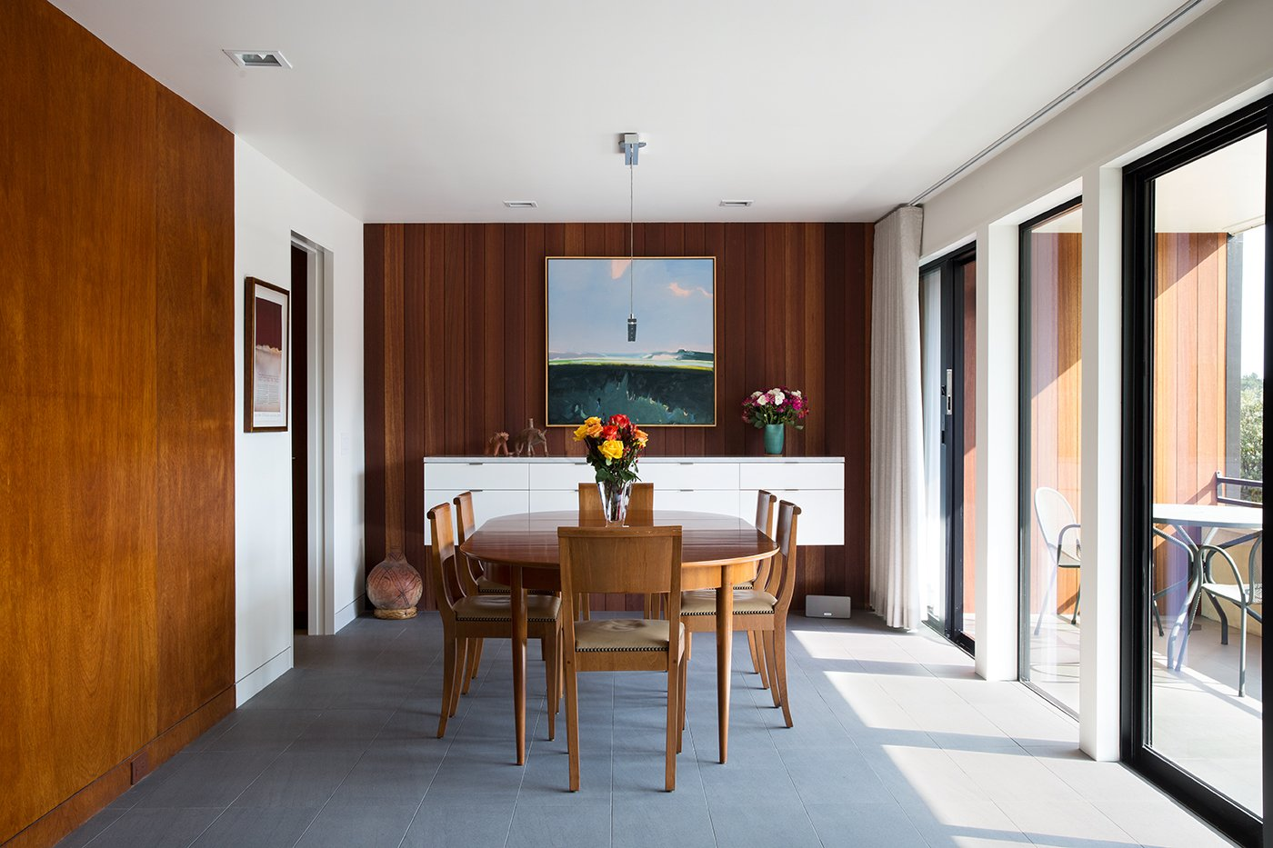 Dining Room, Ceramic Tile Floor, Table, Storage, and Pendant Lighting Mahogany paneling, original to the house, was reused as much as possible.  Photo 2 of 8 in 8 Bright and Airy Wood-Paneled Spaces from Not the Eichler Post-and-Beam Style You Know