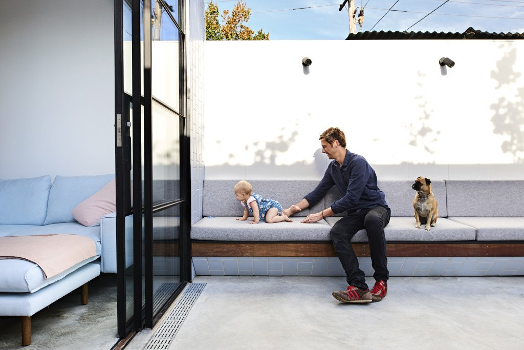 The concrete courtyard offers the family, who four months ago welcomed a second daugther, the option to extend their living space outdoors.  Photo 3 of 11 in It Looks Like a Playland but This Home Works Hard