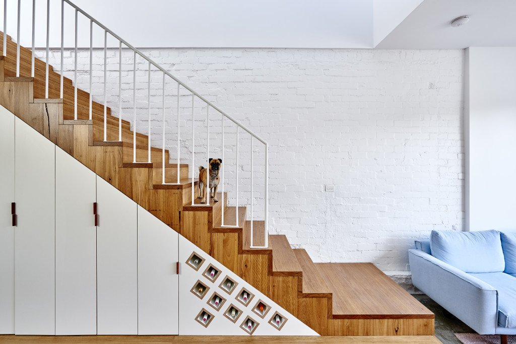 Staircase, Wood Tread, and Metal Railing Each inch is accounted for in the 1,916-square-foot home. Cabinets and clever storage for wine are tucked under the stairs.  Photo 5 of 11 in It Looks Like a Playland but This Home Works Hard