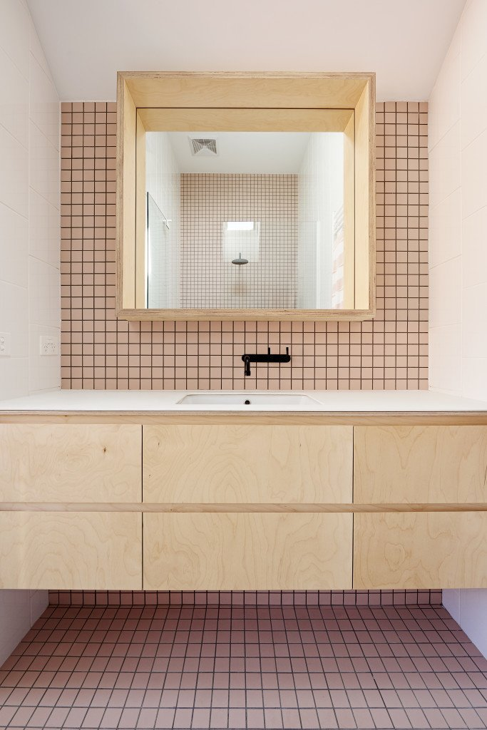 A second bathroom is clad in soft pink tile. All the matte-black fittings in the bathrooms and kitchen belong to the Yokato collection by Brodware.  Photos from It Looks Like a Playland but This Home Works Hard