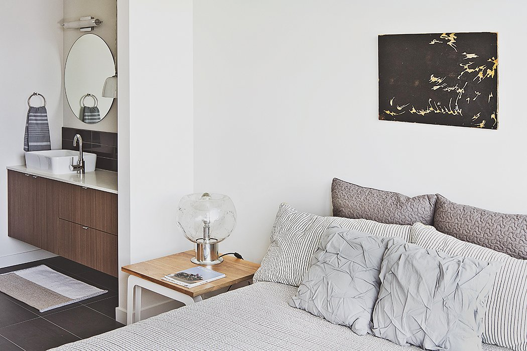 Bowie designed the nightstand, which acts as a prime perch for a vintage lamp her parents purchased in the Netherlands. The wall paint throughout the unit is Eider White by Sherwin-Williams.  Photo 6 of 12 in Three Families Comfortably Fit in One Slim Lot