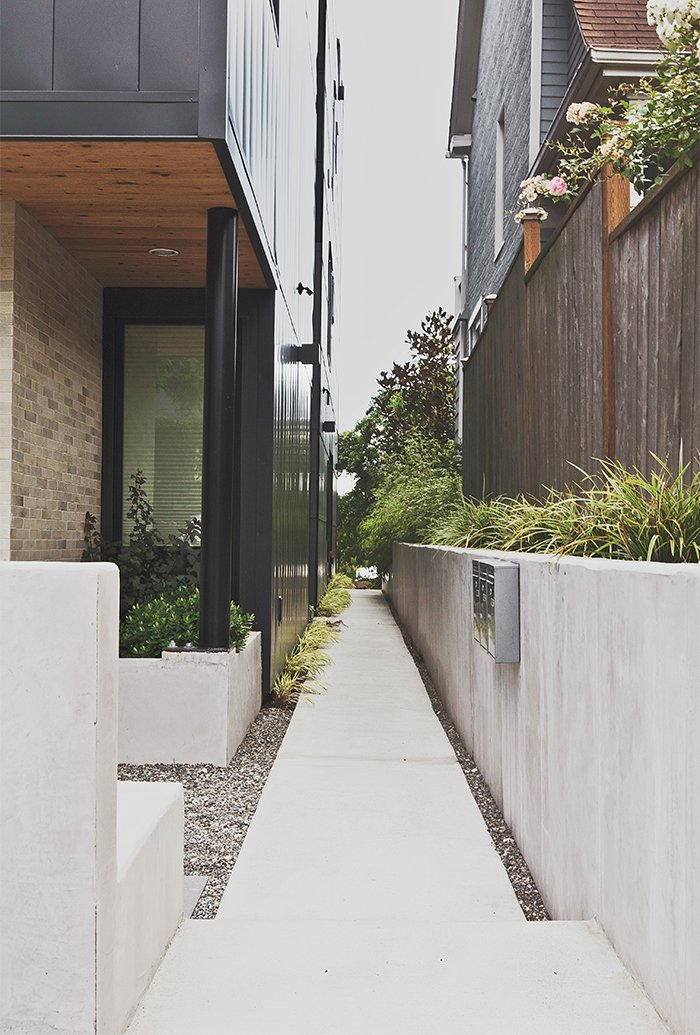 The architects installed concrete pavers on the north and east sides of the house with wooly thyme planted in between.  Photo 10 of 12 in Three Families Comfortably Fit in One Slim Lot