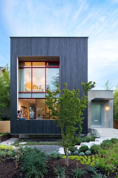 The street-facing facade leans into the landscape with a three-foot-deep cantilever and toward a pathway of hexagonal concrete pavers.