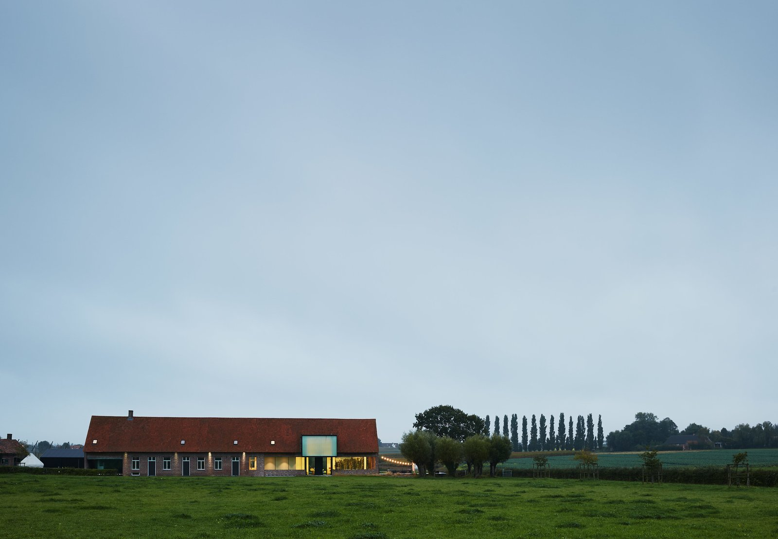 """Exterior, House Building Type, Gable RoofLine, Brick Siding Material, and Shingles Roof Material """"If you want to respect the old, the contrast should be brutal. I want to be very clear what is old and what is new."""" —Dirk Wynants  Photo 2 of 11 in A Kubrick-Esque Farmhouse Kicks Its Fossil Fuel Habit"""