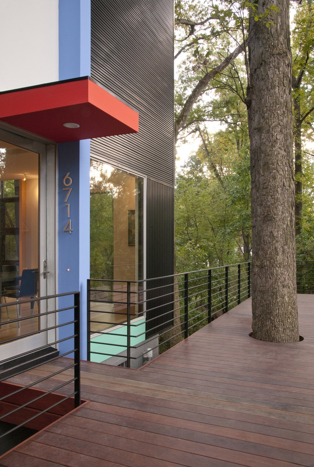 """Outdoor, Small Patio, Porch, Deck, and Wood Patio, Porch, Deck The rivets in the corrugated aluminum siding run both horizontally and vertically. It took time for McInturff to persuade Kanner to embrace the contrast of the lines, but they're pleased with the results. """"The exterior almost looks like a black pair of corduroy pants, but with the stripes going both ways,  Photo 4 of 5 in This Multicolor Facelift Owes Much to Modern Art"""