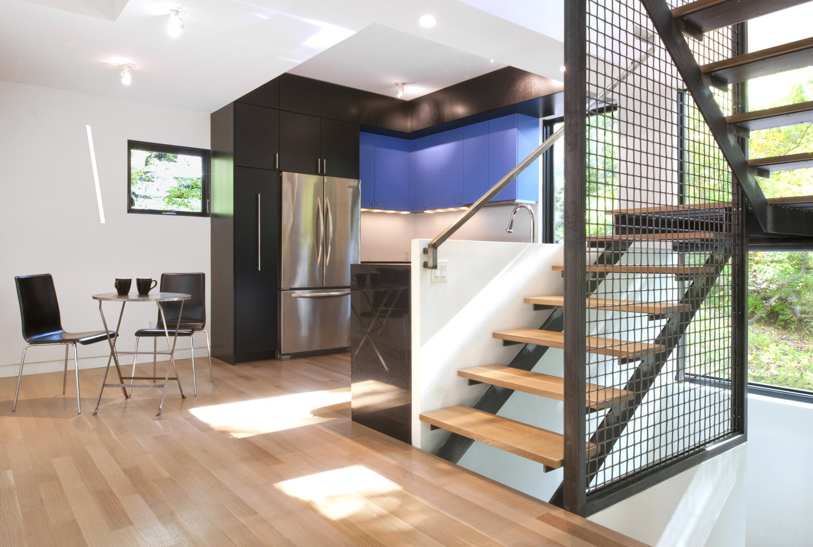 Staircase, Metal Railing, and Wood Tread Inside, where the dining and living spaces were reconfigured, the vibrant colors continue with smaller accents like the azure cabinetry.  Photo 5 of 5 in This Multicolor Facelift Owes Much to Modern Art