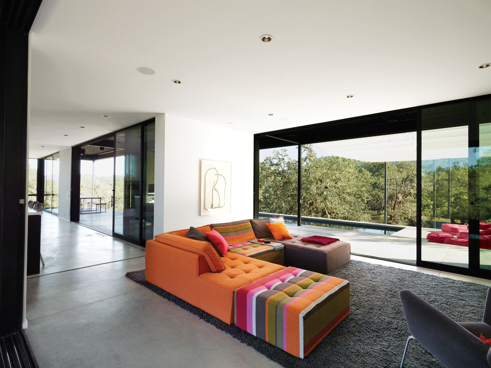 The Mikado 2 sofa by Hans Hopfer for Roche Bobois is a bright and cheery centerpiece in the otherwise sedate living room. The nubby wool Photon rug from Design Within Reach warms up the expanse of concrete. The framed drawing is by the Los Angeles–based artist Daniel Brice. Huge sliding doors open the house to the outdoors and virtually double the Burtons' living space.  Photo 5 of 8 in When Prefab Is Painless