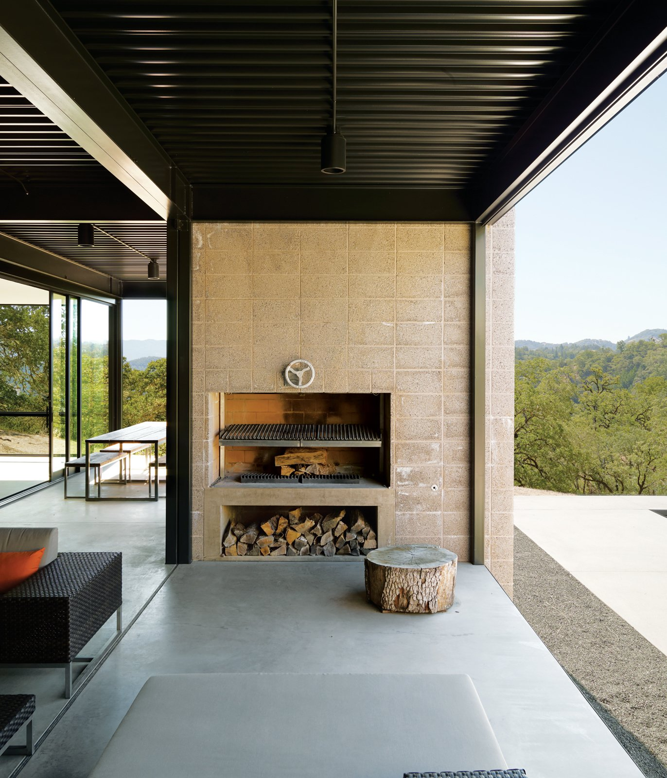 Passionate cooks, the Burtons installed a Mugnaini wood-fired oven in their kitchen and had a custom Grillery fireplace-barbecue built into the concrete block wall on their deck. Beneath the grill they store oak firewood collected from their property.  Photo 6 of 8 in When Prefab Is Painless