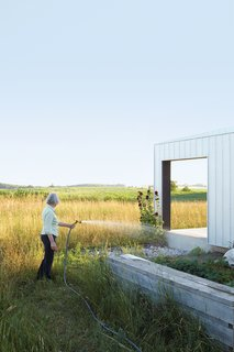 Maggie Treanor waters plants around her rural home.