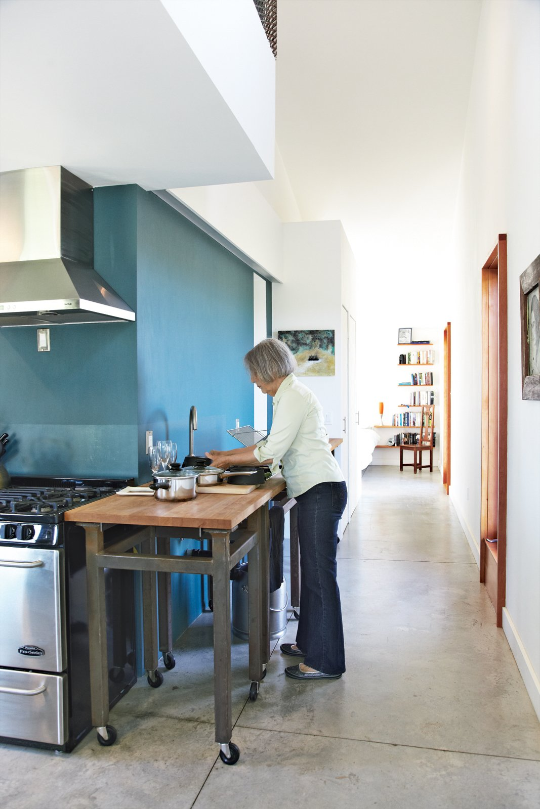 Kitchen, Concrete Floor, and Wood Cabinet Though small, Treanor's house feels spacious thanks to an open kitchen and a tranquil mezzanine.  Photo 7 of 11 in An Off-Grid Home That Relies on the Sun and the Wind