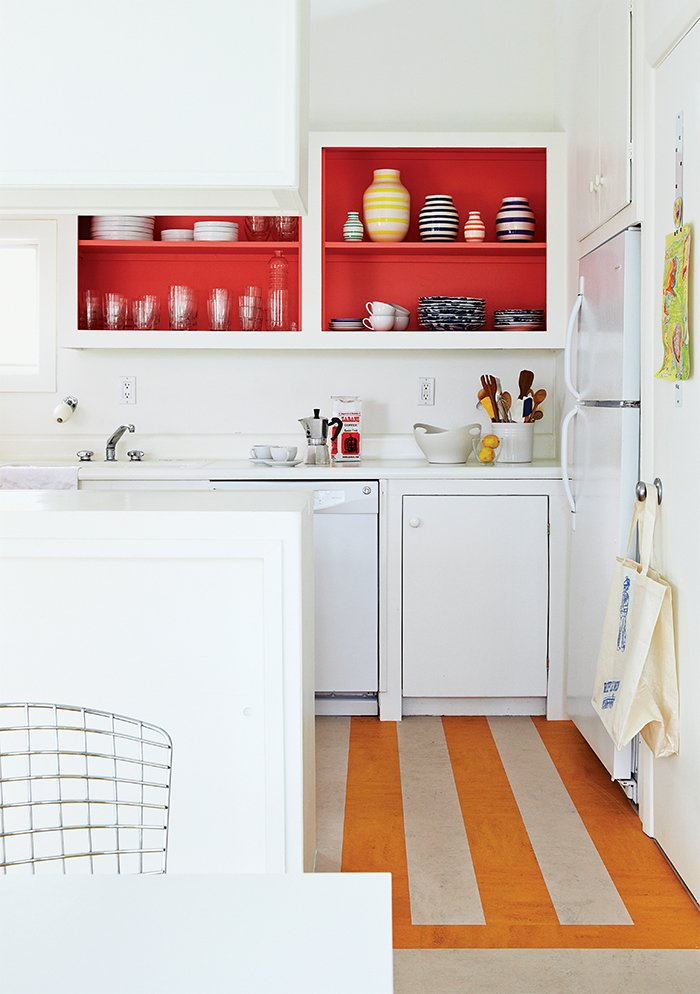 In the kitchen, Angle removed the cabinet doors and applied a coat of Poppy Red paint by Benjamin Moore, and put down a striped linoleum floor to brighten the space.  Photo 5 of 9 in How a Smart Interior Design Saved This House