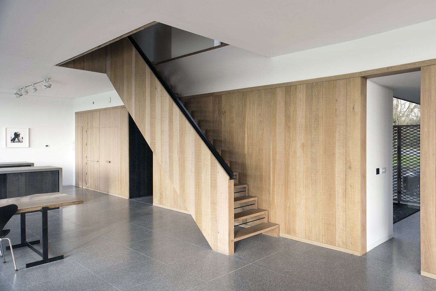 A palette of natural materials is employed in both the interior and exterior. An oak wall and staircase, designed by Jeremy Pitts, join a floor made of gray terrazzo tile.  Stairways from Bold House Doubles as a British Town's Welcome Sign