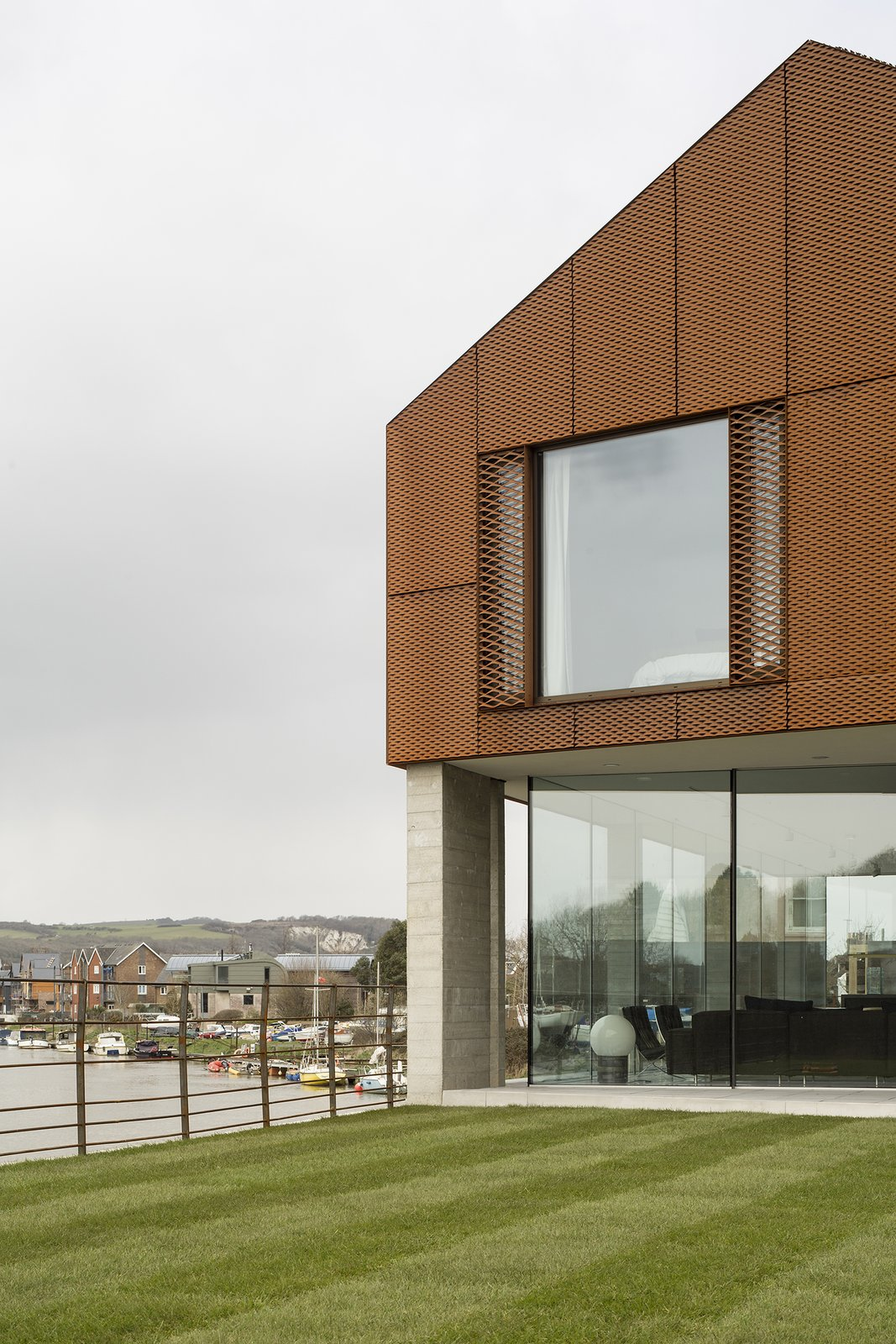 The upper story is clad in a decorative rainscreen of Cor-Ten steel mesh, chosen in part for its tone, which complements the red clay brick used locally.  Photo 6 of 7 in Bold House Doubles as a British Town's Welcome Sign