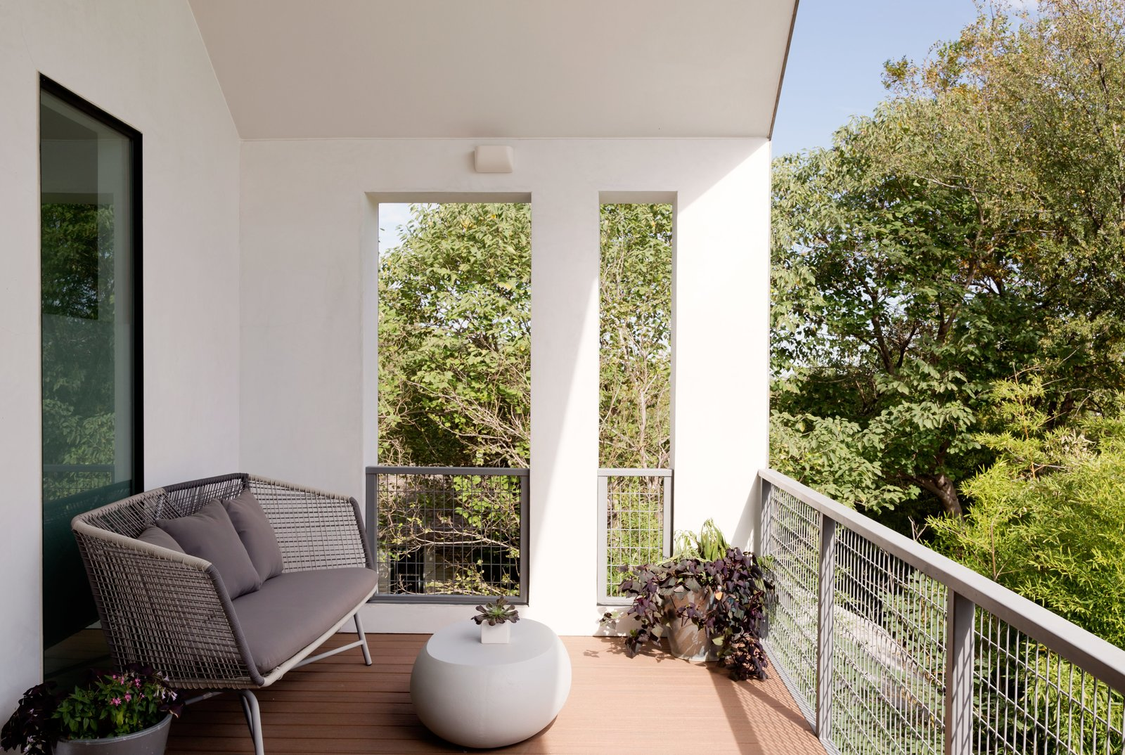 Outdoor, Metal Fences, Wall, and Wire Fences, Wall A covered deck off the master bedroom with a Huron sofa by West Elm provides another spot to take in the city's pleasant days.  Photo 5 of 6 in Refreshed Take on the Gable Shines in Austin's Building Boom