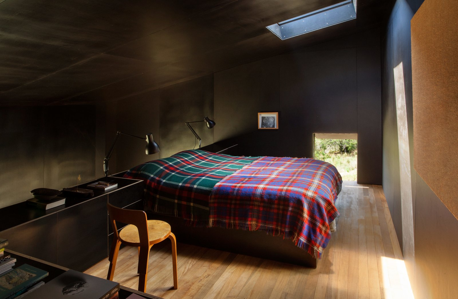 """Bedroom, Bed, Chair, Lamps, and Night Stands The formply used to line the black interior creates a """"small, inky bubble of space,"""" Cheshire says. """"It's incredibly calm and quiet as a consequence."""" His firm designed the built-in bed and cabinetry. The two Type 75 lamps are by Kenneth Grange for Anglepoise, and the Chair 65 is by Alvar Aalto.  Photo 5 of 7 in Two Tiny Cabins Chose Simplicity Over Size"""