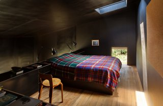 "The formply used to line the black interior creates a ""small, inky bubble of space,"" Cheshire says. ""It's incredibly calm and quiet as a consequence."" His firm designed the built-in bed and cabinetry. The two Type 75 lamps are by Kenneth Grange for Anglepoise, and the Chair 65 is by Alvar Aalto."