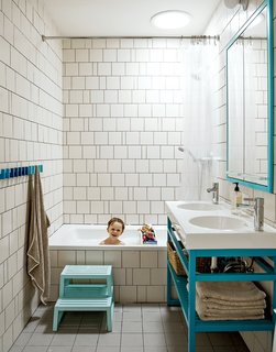 "A creative way of cutting costs is on display in son Nate's bathroom, where the wall tiles are arranged in a whimsical, irregular pattern making use of slim sections of tile cut for transitions and corners. ""We came up with a pattern that could incorporate random sizes so we were able to order the exact amount of tile that we needed,"" Bischoff says. ""It allowed us to get the most out of the tile price because there wasn't that 20 percent that [would normally go] into the landfill."" The two-bowl sink is the Vitviken model from Ikea; it's topped with a chrome Hansgrohe faucet and accented by Ikea's Godmorgon medicine cabinets customized by MADE."