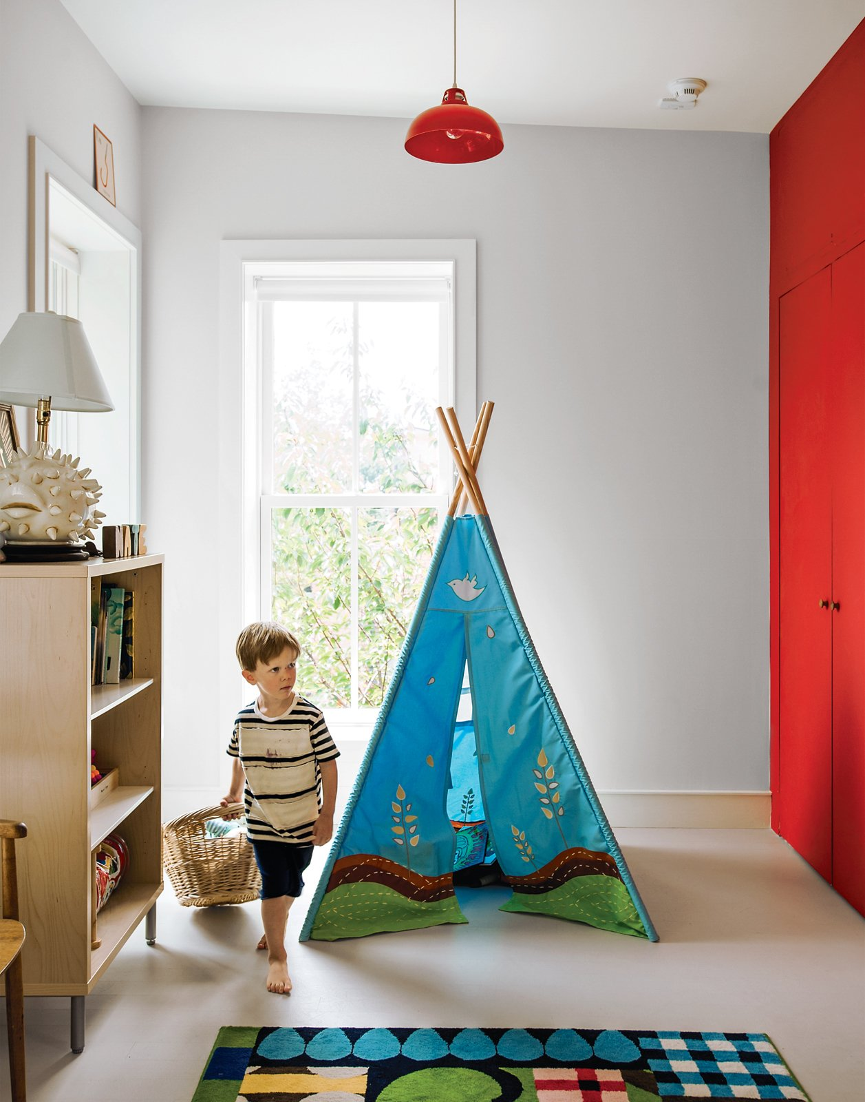 """Kids Room, Bedroom Room Type, Storage, Toddler Age, and Boy Gender Now three, Nate occupies coveted corner real estate in a third-floor room with a treetop-level view. """"It's a great space,"""" Casale says, """"although it is the noisiest room in the house because of the street. But by now he's so used to sleeping through all of the sounds, I don't think it bothers him."""" The brightness of the space is enhanced by an accent wall coated in fire engine–red chalkboard paint (Benjamin Moore Natura flat-finish paint in Vermillion mixed with unsanded grout) that Nate can scribble on—as soon as his parents get around to telling him that it's allowed. A matching red pendant lamp from the Soho shop Kiosk hangs above a six-foot-tall teepee by Dexton Kids.  Photo 8 of 9 in The Brownstone Baked to Perfection"""