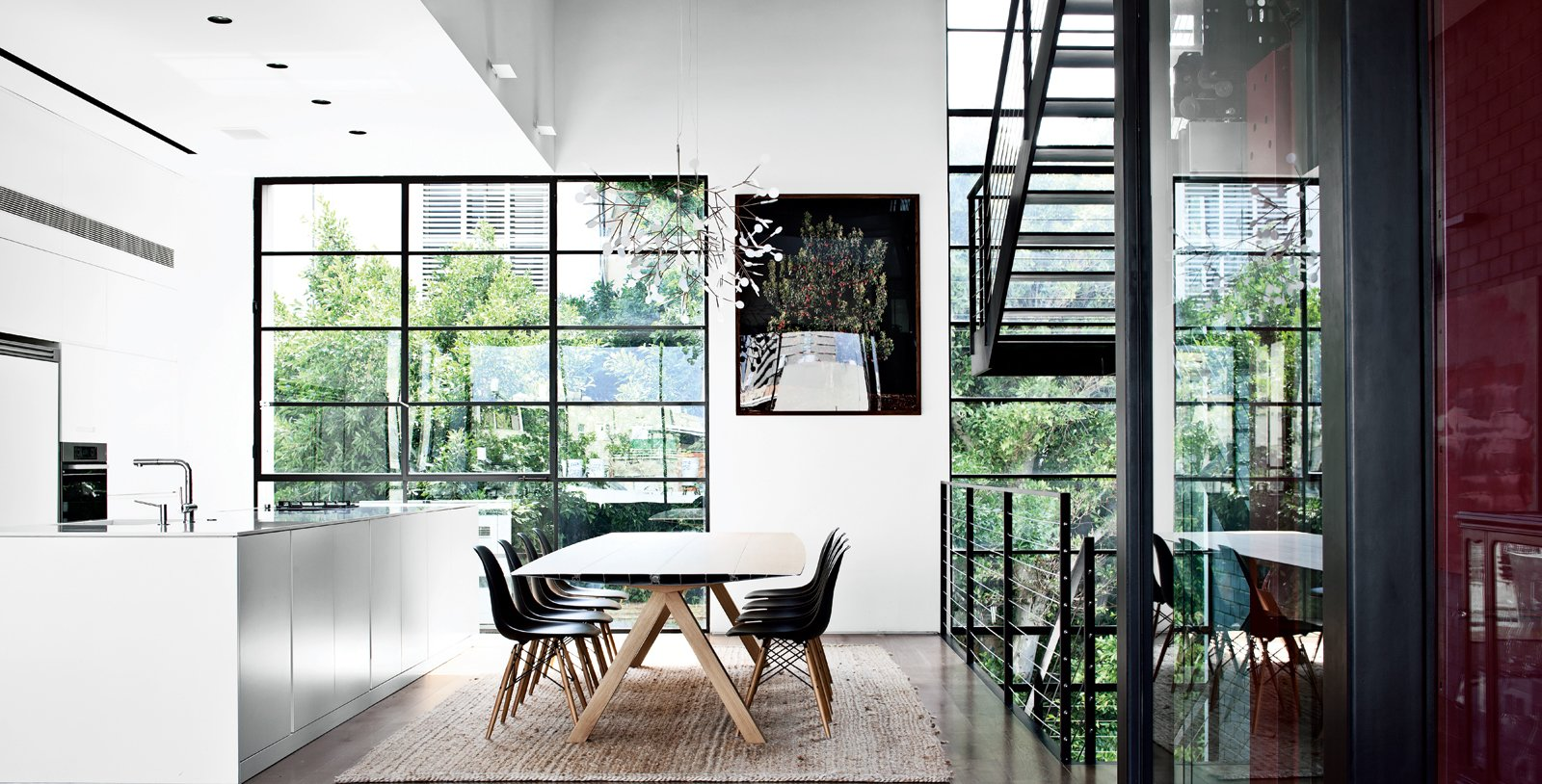Dining Room, Table, Chair, Rug Floor, and Medium Hardwood Floor The family eats at Table B by Konstantin Grcic for BD Barcelona. The Plastic side chairs are by Charles and Ray Eames for Vitra.  Photo 7 of 8 in Modern High-Rise Town House in Tel Aviv