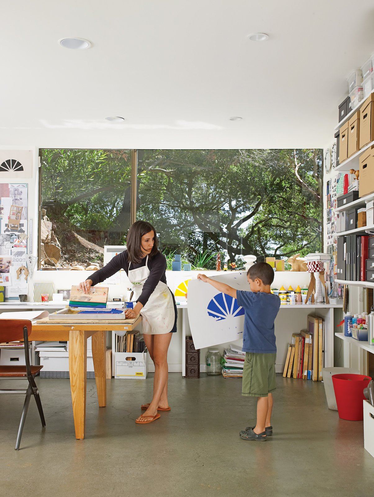 Office, Craft Room Room Type, Shelves, and Concrete Floor Verda Alexander and her son, Apolo, collaborate on a project in their first-floor studio.  Photo 2 of 20 in You Don't Have to Just Be at Your Desk When Working from Home