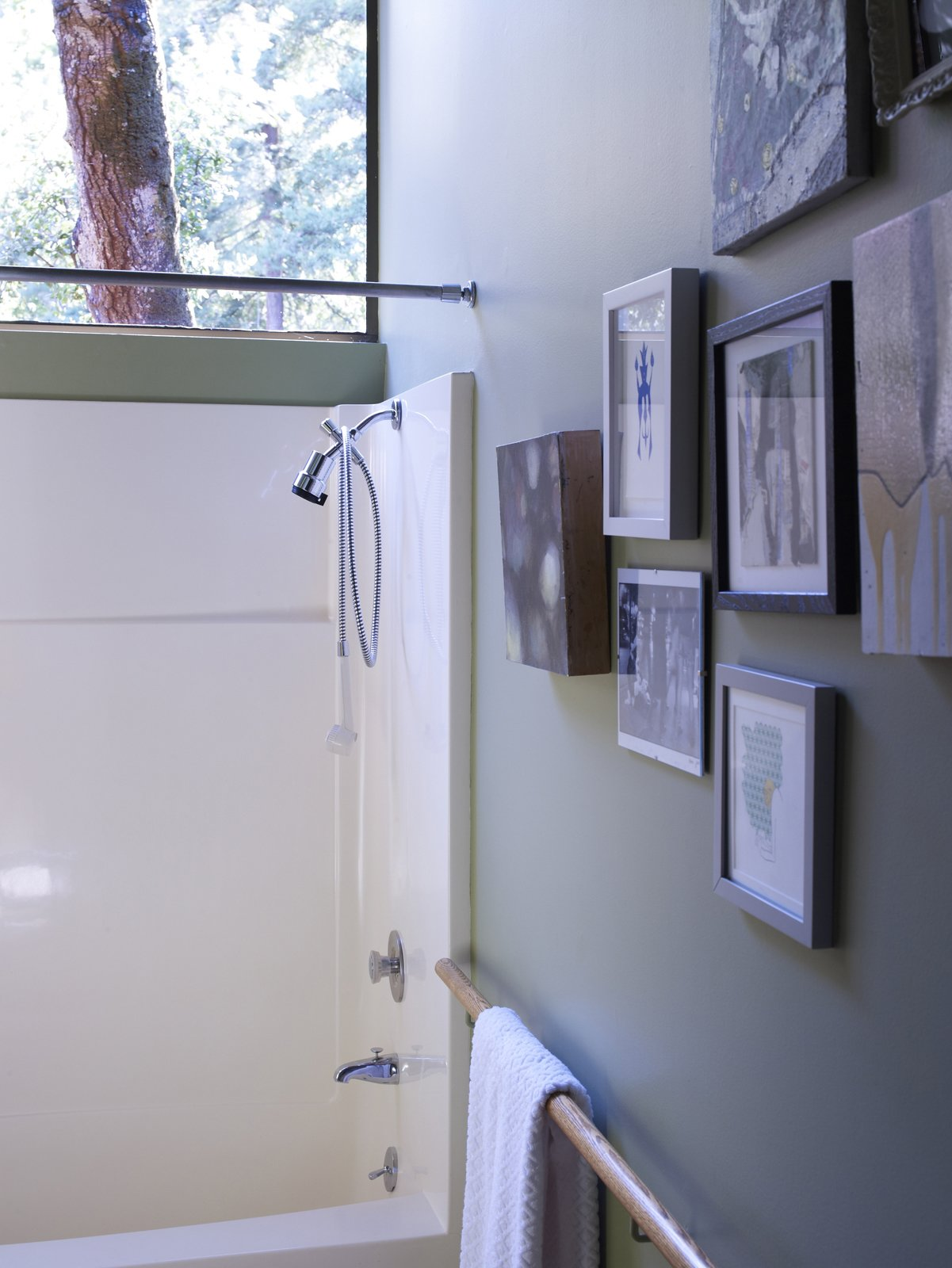 A salon-style hanging of art and the wooden handrail-cum-towel rack give the bathroom a handful of subtly stylish touches.  Photo 14 of 20 in You Don't Have to Just Be at Your Desk When Working from Home