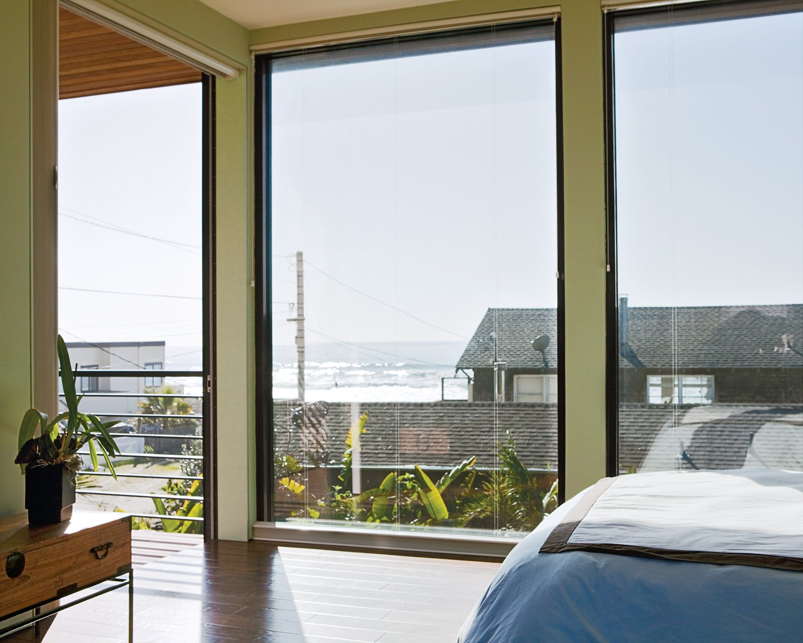 Bedroom and Bed Floor-to-ceiling windows in the bedroom create the sensation of being outside, as if the entire house is one platform deck strategically shielded from the elements.  Photo 6 of 11 in Rising Tides Are No Match for This Coastal Home