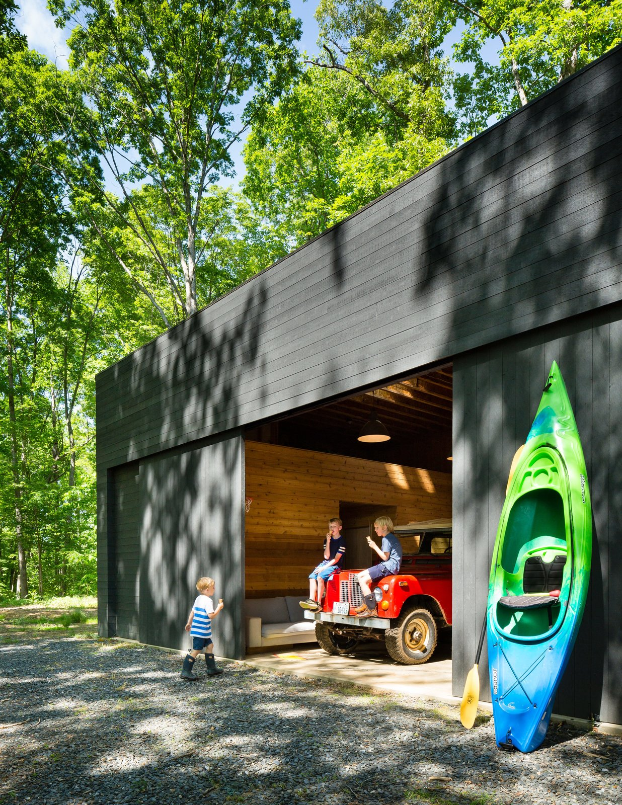 Garage The spacious detached garage stows a bevy of kayaks and inner tubes, not to mention the family car.   Photo 4 of 9 in Three Joined Cabins Turn This Virginia Retreat Into a Modern Take on Camp