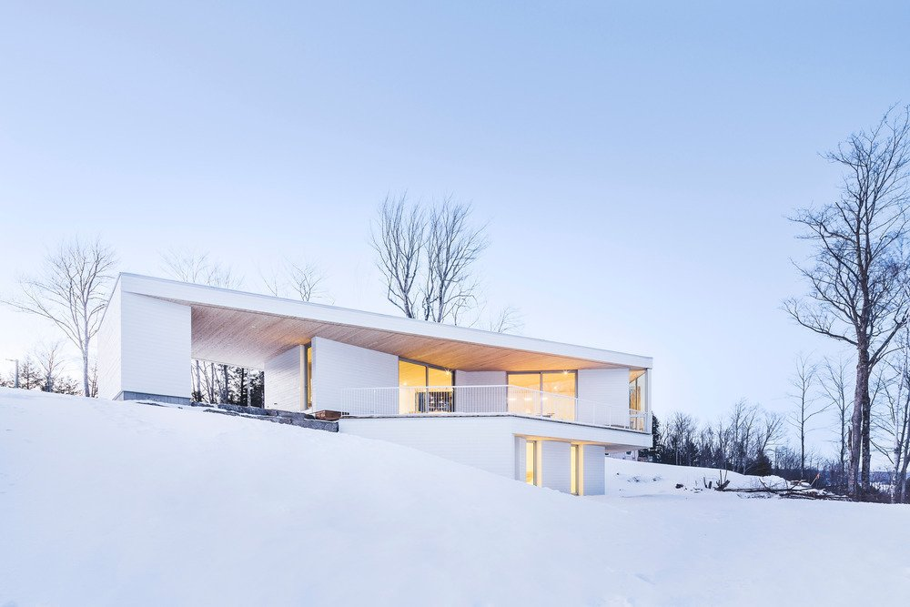 Exterior, Metal Roof Material, Flat RoofLine, House Building Type, and Wood Siding Material Squinting through Quebec's seasonal fluries, one might not immediately register the Nook Residence, an all-white retreat that purposefully blends into the winter landscape. The house, designed by MU Architecture, presents itself to passersby as a blank monolith; yet around the corner, it opens onto Lake Memphremagog through expansive windows and an interior balcony.
