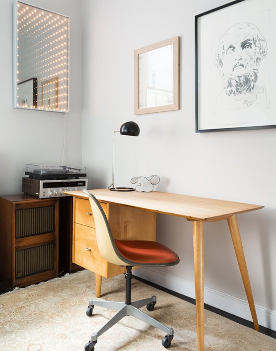 Office, Desk, Chair, and Rug Floor In the office, a 1950s desk by Paul McCobb is complemented by an Eames chair and the Boi desk lamp by David Weeks Studio. The lighted mirror is a piece called  Photo 5 of 7 in 725 Square Feet and Loads of Modern Gems