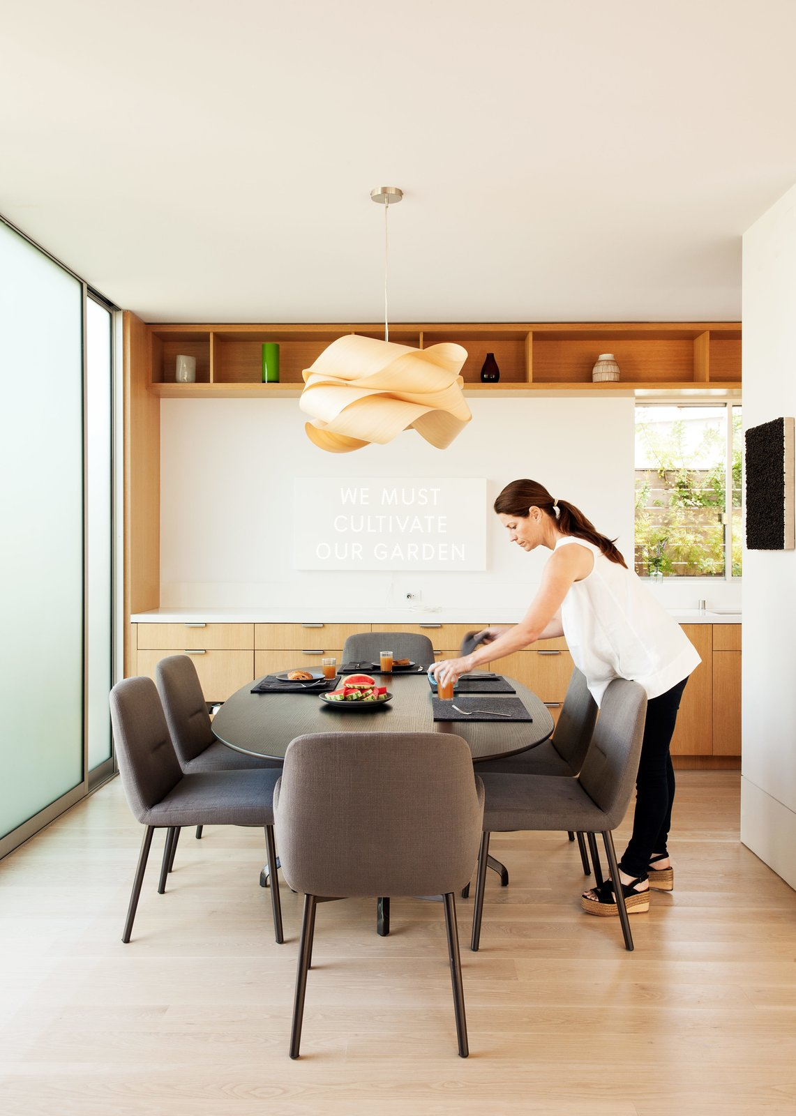 Dining Room, Chair, Light Hardwood Floor, Pendant Lighting, and Table A EuroStone countertop structures the open-plan kitchen and dining room, where the family will often gather and play.  Best Photos from Amid a Hotbed of Architecture, This Home Holds Its Own